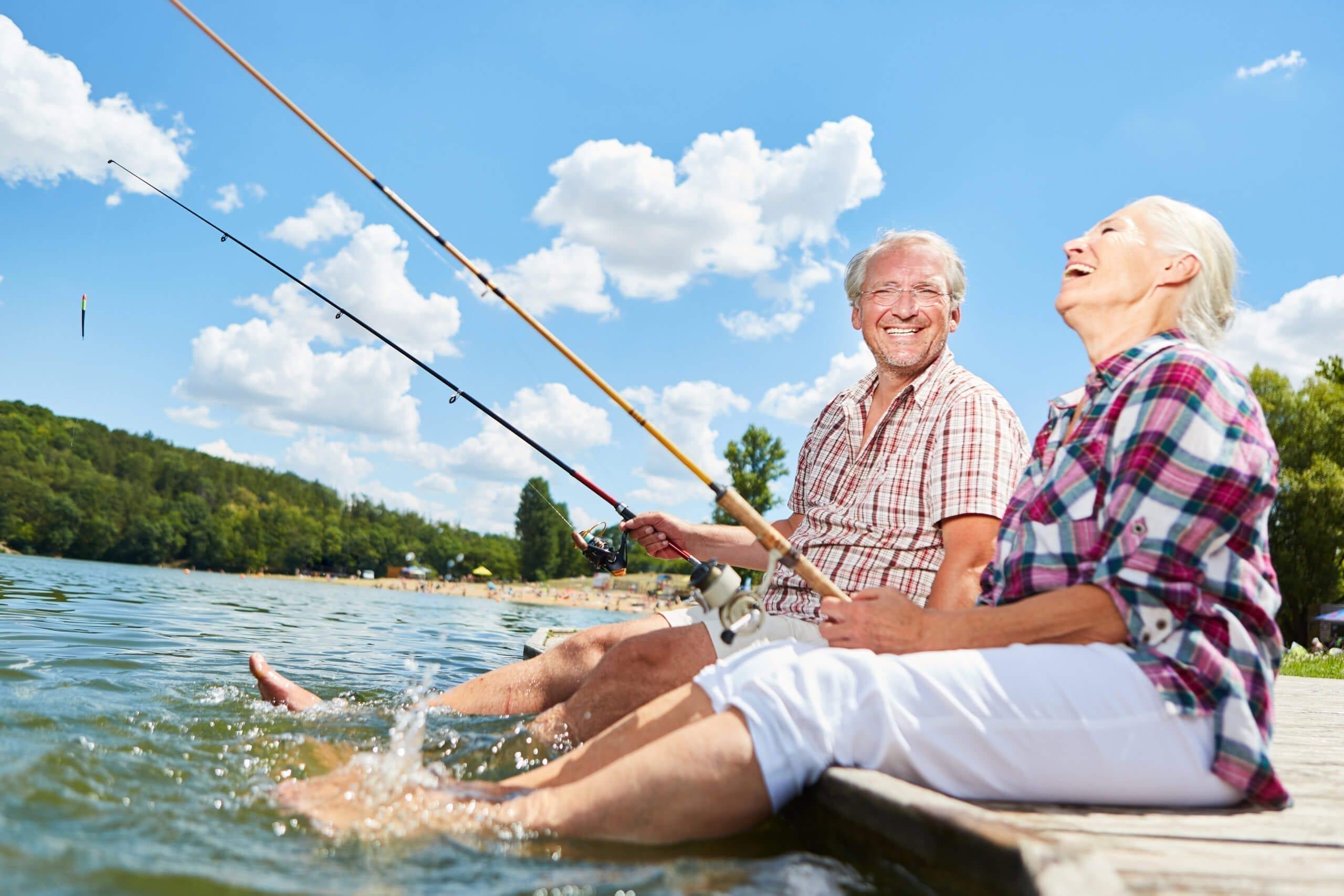 Senior Paar plantscht mit den Füßen im Wasser beim Angeln am See im Sommer